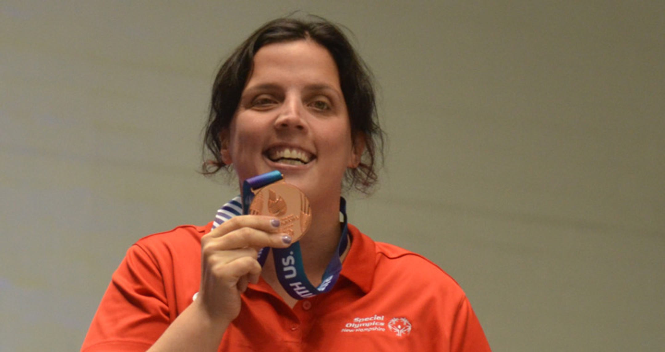 Athlete proudly smiling while holding up a medal